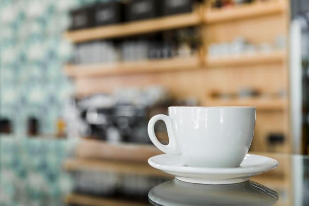 反射ガラス上のコーヒーのカップ