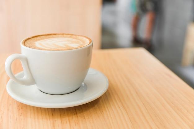 木製のテーブル上のカプチーノのコーヒーの上にアートラテのカップ