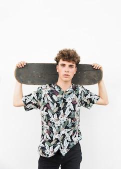 白い背景の上に隔離された彼の肩にスケートボードを持っている笑顔の男