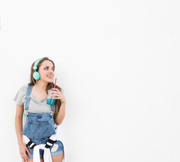 白い背景上に離れて見えるヘッドホンを着ているジュースのガラスを保持している女性