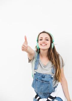 白い背景にサムネイルサインを表示している幸せな若い女性