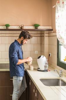 キッチン、コーヒーを準備する男の側面図