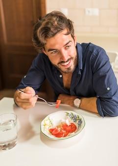 Улыбающийся молодой человек, есть салат с вилкой