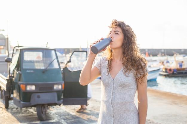 Молодая женщина питьевой воды из бутылки стоит возле побережья