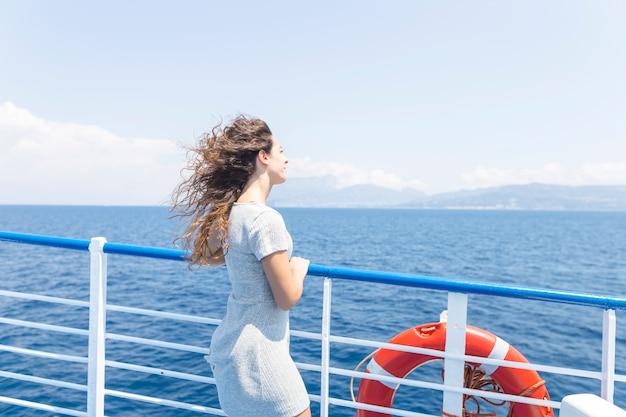 青い海を見て船の手すりの横に立っている若い女性