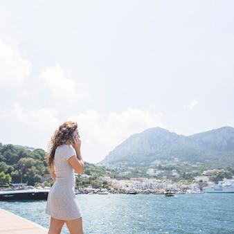 携帯電話で話している桟橋に立っている女性