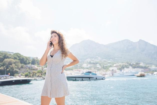 Улыбаясь молодая женщина, стоящая возле дока, говоря на сотовый телефон