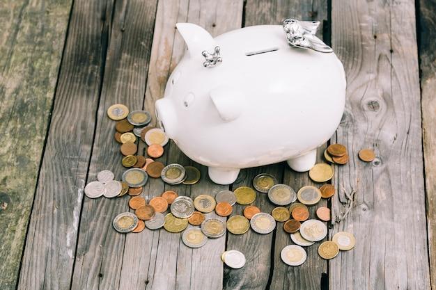 古い木製のテーブルの上に白いピギーバンクの周りのコイン