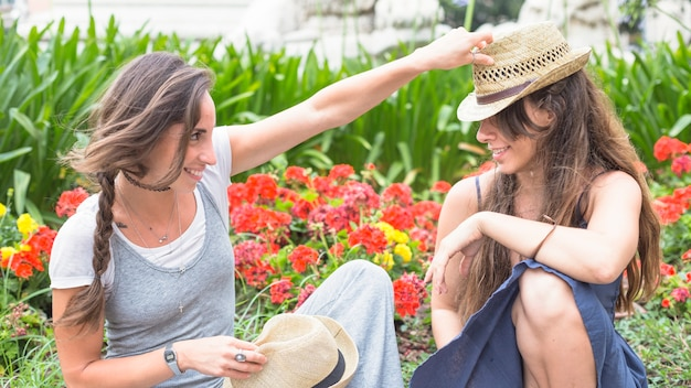 庭に座っている彼女の友人の帽子の上に帽子