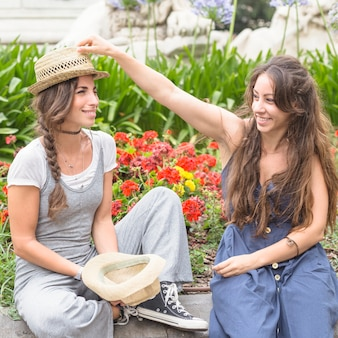 彼女の友人の頭の上に麦わら帽子を置く幸せな友人公園