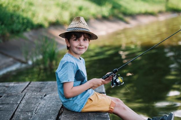 湖で帽子釣りをしている幸せな少年の側面図