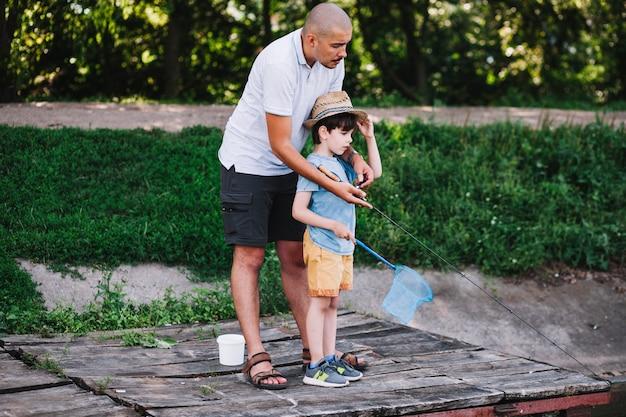 彼の父と釣りをする少年