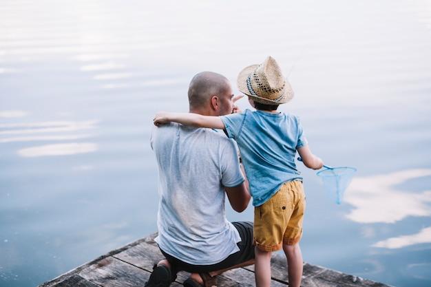 湖の近くで漁網を保持している彼の息子と漁師