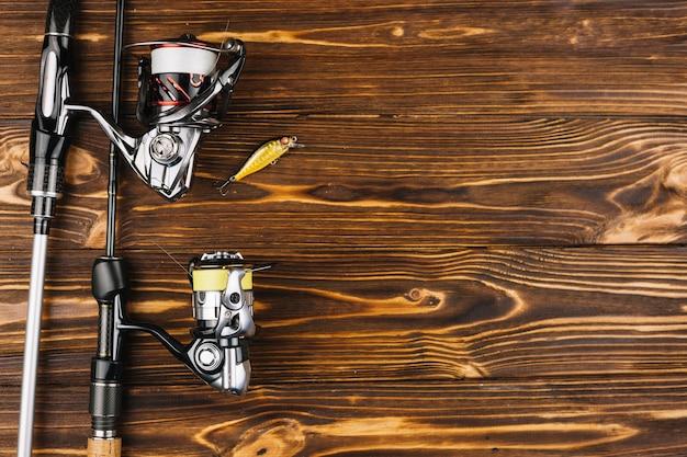 木製の背景に釣り竿と餌のオーバーヘッドビュー