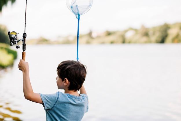 湖の近くで釣り竿とネットを持っている少年
