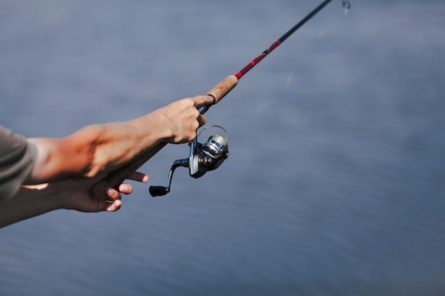 釣りロッドで漁師の手のクローズアップ