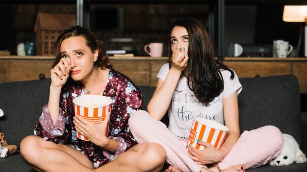Женские друзья получают эмоциональное во время просмотра фильма