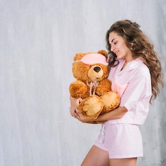 柔らかいおもちゃを持っている若い女性の側面図