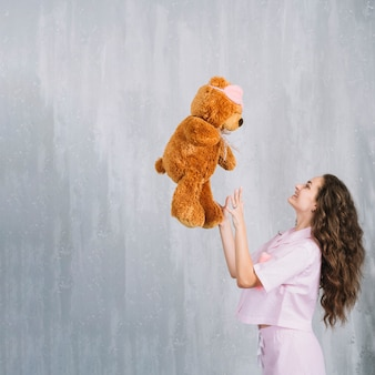 Вид сбоку улыбается молодая женщина, бросая мягкую игрушку в воздухе