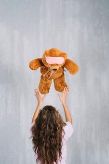 空中で柔らかいおもちゃを投げている若い女性のリアビュー