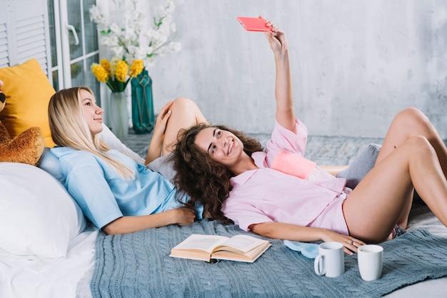 ベッドでリラックスして携帯電話でセルフをする女性の二人の友人