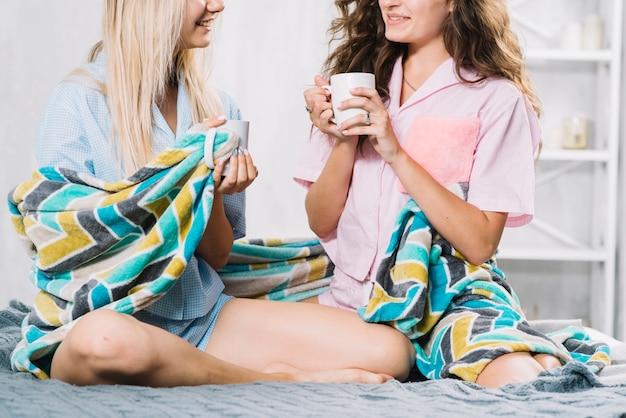 Две подруги, сидя на кровати, пить кофе