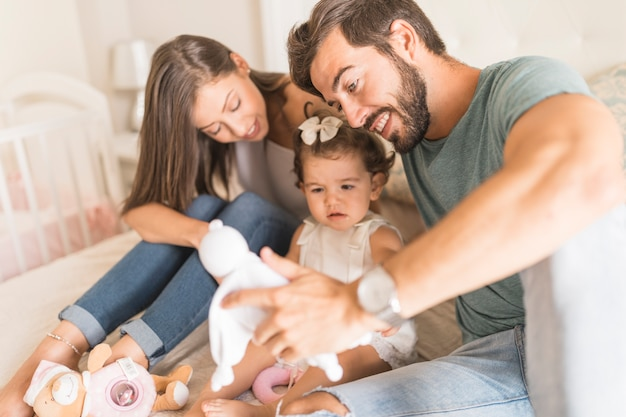 Родители, предлагающие игрушки дочери