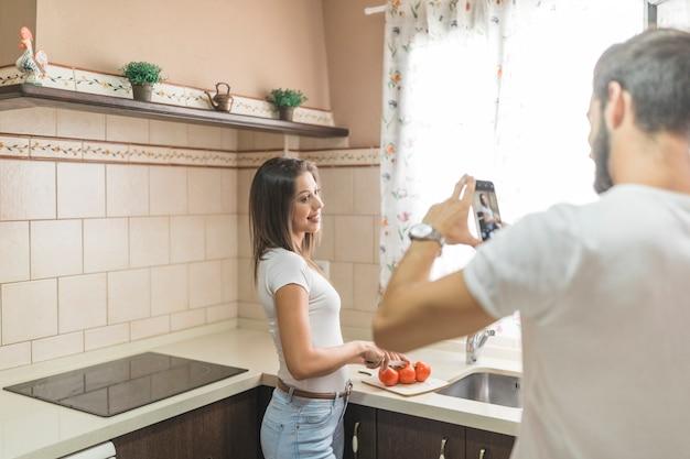 匿名の男は、キッチンでガールフレンドの写真を撮る