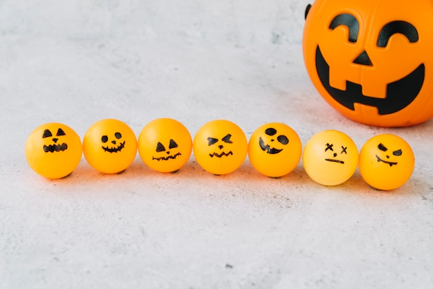 Композиция с небольшим оранжевым шаром с жуткими лицами в ряду