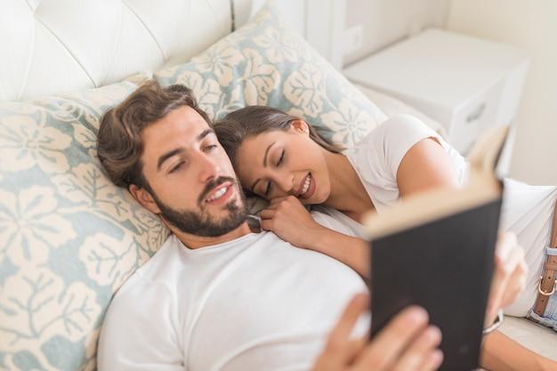 Бородатый человек читает книгу возле спящей подруги