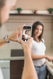 キッチンで女性の写真を撮る男