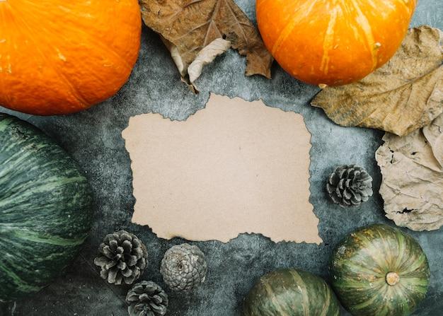 葉とコーンのあるカボチャの中で紙を真ん中に燃やす