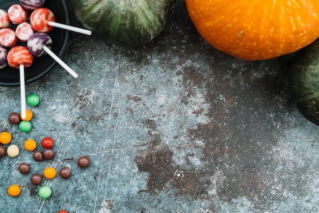 上に横たわるカボチャの横に横たわるハロウィーンのお菓子