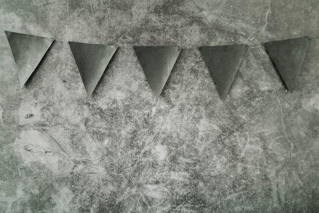 灰色の背景にぶら下がっている三角の黒の装飾の旗