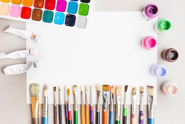 Различные краски и щетки возле пустой бумаги