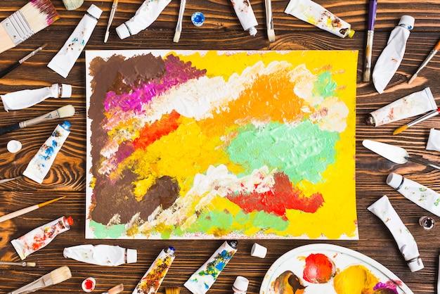 抽象絵画の周りのチューブとブラシ