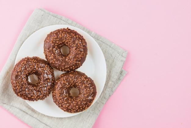 灰色の材料上のプレート上のチョコレートドーナツ