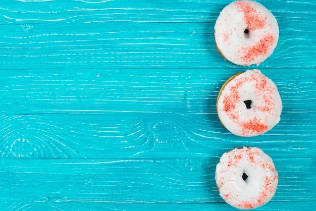木製の背景に新鮮な砂糖の甘いドーナツ