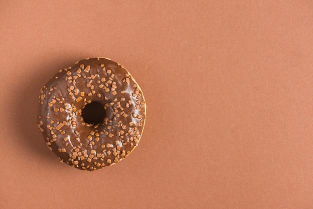 スプリンクラーで飾られた甘いチョコレートグラスドーナツ