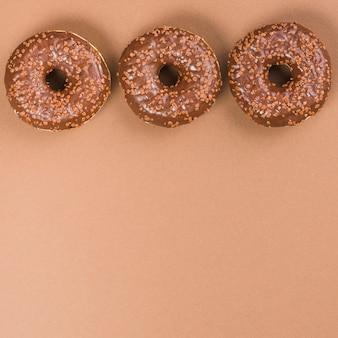 茶色の背景に丸く霜付けドーナツ