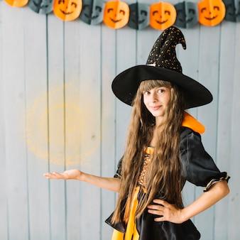 ハロウィーンの魔法使いを見せている若い魔女