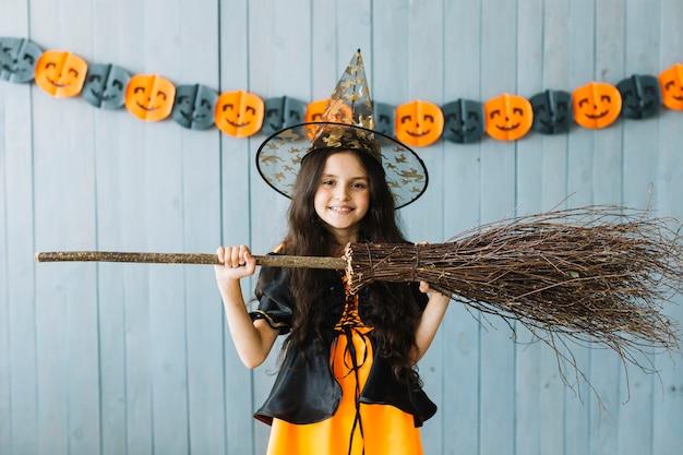ハロウィーンの衣装の前で十代の女の子はほうきを保持する