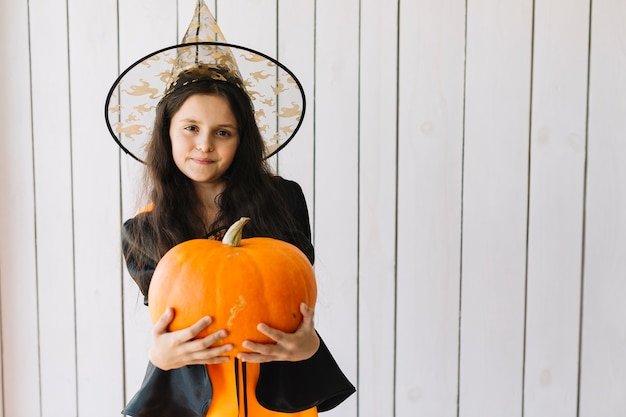 Девушка в костюме хэллоуина с тыквой в студии