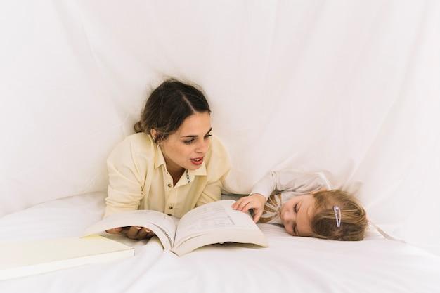 Женщина, читающая книгу для спящей дочери