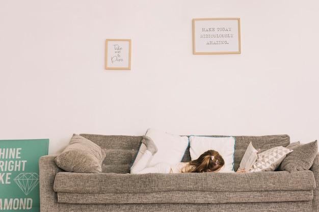 匿名の女の子がソファで読書する