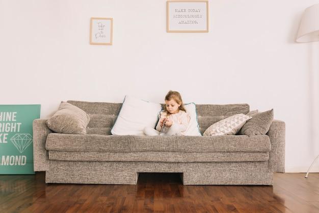 素敵な女の子がソファで読書する