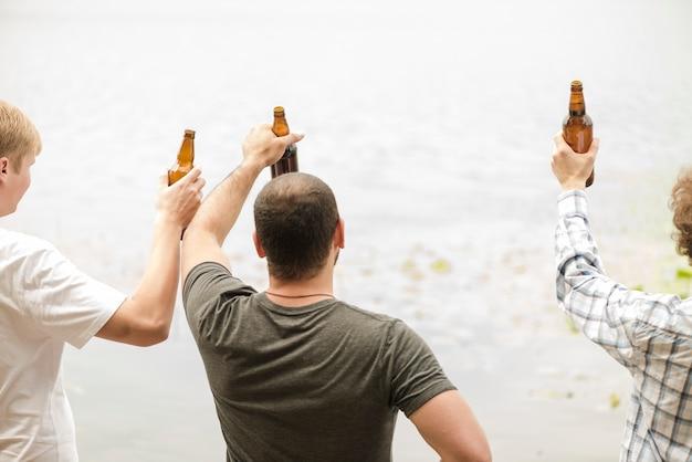 水の近くでビールを飲む男性