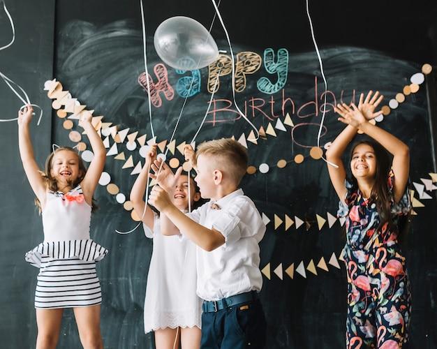 Веселые дети выпускают воздушные шары на вечеринке по случаю дня рождения