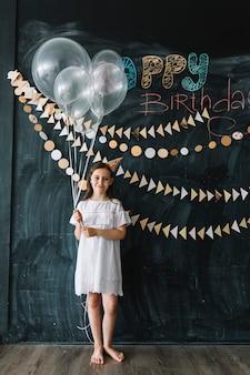 Девушка с воздушными шарами на вечеринке по случаю дня рождения
