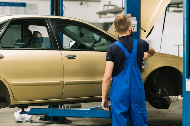 ロックリフトの近くに立つ自動車整備士